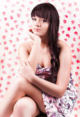 Beautiful brunette girl with tress in dress sitting — Stock Photo