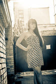 Portrait of sexy brunette girl in dress posing against brick wall — Stock Photo