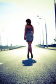 Foto de mujer delgada sexy caminando por la carretera vacía — Foto de Stock