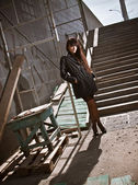 Sexy woman in black standing near stairs on street — Stock fotografie