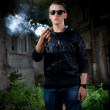 Portrait of young man in sunglasses smoking marijuana joint  — Stock Photo