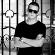Man in black t-shirt and sunglasses leaning to metal fence — Zdjęcie stockowe