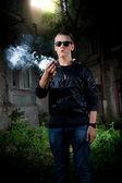 Portrait of young man in sunglasses smoking marijuana joint — Stok fotoğraf