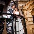 Newly married couple hugging on balcony of old building — Stock Photo