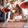 Portrait through glasses of dating couple kissing in restaurant — Foto de Stock