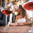 Portrait through glasses of dating couple kissing in restaurant — Lizenzfreies Foto