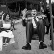 Photo of newly married couple swinging on playground — Stock Photo