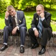 Sad men in suits sitting on bench in park and thinking — Stock Photo #35684939