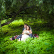 Newly married couple sitting on green lawn under big tree — Stock Photo