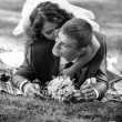 Portrait of young bride kissing groom lying on grass at park — Stock Photo