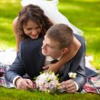 Young bride lying on grooms back at park and hugging him — Stock Photo
