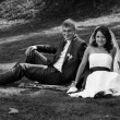 Bride and groom sitting back to back on grass at park — Stock Photo