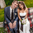 bride and groom sitting close to each other on bench — Stockfoto