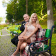 Young couple sitting on bench at park and looking at camera — Stockfoto