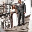 Bride and groom holding hands and walking down the stairs — Stock Photo