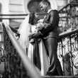 Bride and groom standing on stairway and looking at each other — Stock Photo