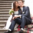 Stock Photo: Brunette bride sitting on stairs and kissing groom in cheek