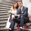 Stock Photo: Young bride and groom sitting on stairs and hugging