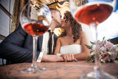 Portrait through glasses of dating couple kissing in restaurant — Stock Photo