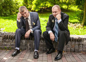 Sad men in suits sitting on bench in park and thinking — Stock Photo
