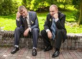 Traurige Männer in Anzügen sitzen auf Bank im Park und denken — Stockfoto