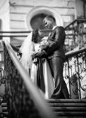 Bride and groom standing on stairway and looking at each other — Stockfoto