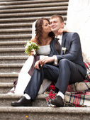 Brunette bride sitting on stairs and kissing groom in cheek — Stock Photo