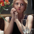Elegant blonde woman sitting at the table at restaurant — Stock Photo
