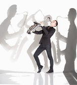 Saxophonist playing against background with shadow of musicians — Stock Photo