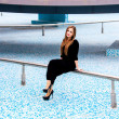 Woman in black dress sitting on pipe of empty fountain — Stock Photo