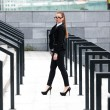 Woman in black suit walking on stairs with railings at street — Stock Photo #35867371
