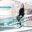 Businesswomsitting on railings against city view — Stock Photo #35867379