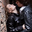 Portrait of handsome man pushes sexy woman against brick wall — Stock Photo