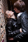 Portrait of handsome man pushes sexy woman against brick wall — Foto de Stock