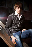 Young man in jeans sitting on street at night — Stock Photo