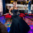 Girl in long dress sitting on chair at dance floor of nightclub  — Stok fotoğraf