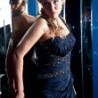 Portrait of sexy woman in blue dress leaning against mirror wall — Stock Photo