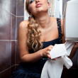Sexy blond woman tearing off toilet paper at lavatory — Stock fotografie