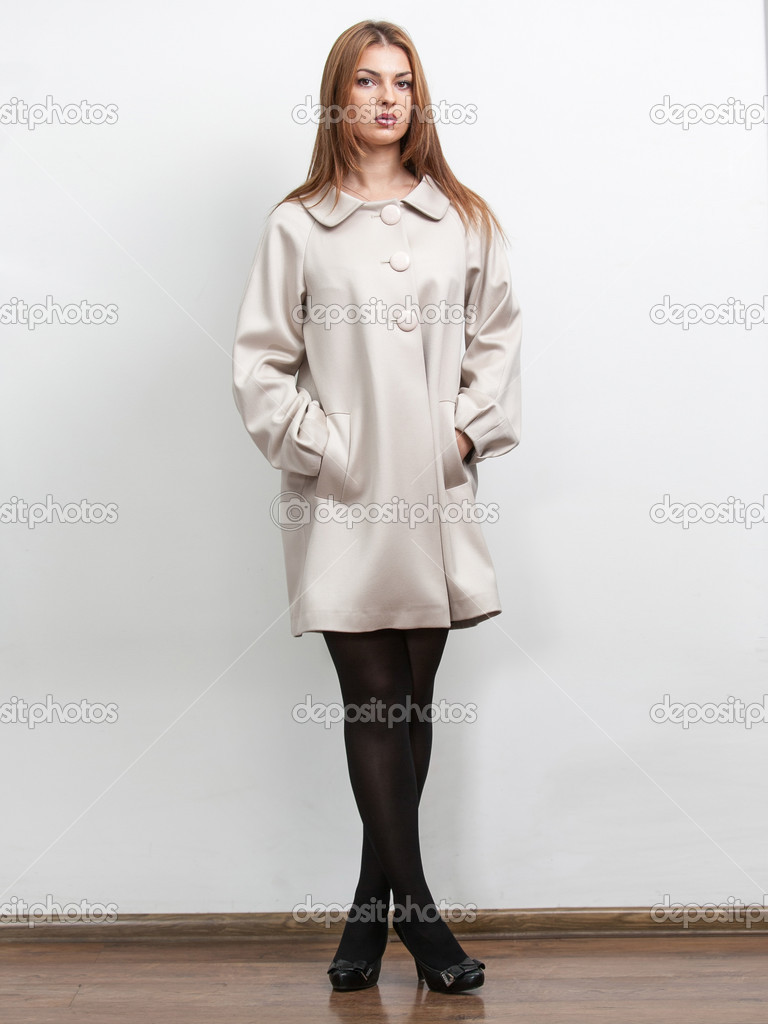 Woman wearing white short coat and holding hands in pockets ...