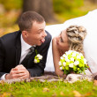 Bride and groom lying on grass at park and making funny faces — Stock Photo