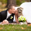 Newly married couple lying on grass at park and kissing — Stock Photo