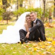 Newly married couple sitting on grass at autumn park — Stock Photo
