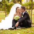 Bride looking at grooms eyes while sitting on grass at park — Stock Photo