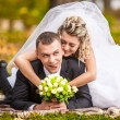 Newly married couple lying on grass in park and having fun — Stock Photo