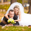 Beautiful bride and groom lying on grass and smiling at camera — Stock Photo