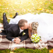 Married couple lying in park on plaid and kissing passionately — Stock Photo