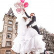 Bride and groom flying on helium balloons in city — Stock Photo #36336057