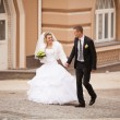 Bride and groom walking on paving road at old city — Stock Photo