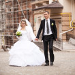 Bride and groom holding hands and walking in old city — Stock Photo