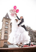 Bride and groom flying on helium balloons in the city — Stock Photo